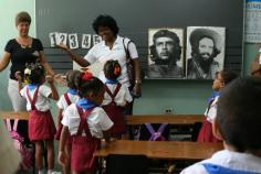 Sarah Daisy interacts with a group of school children. The pictures of Che and Fidel are typical of all schools and public buildings.
