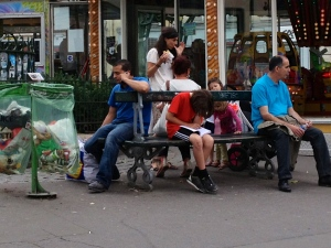 Our son reads a book on a park bench on Rue des Abesses in Paris, completely at home with his French comrades.